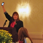President Linda Lord Jenkins holds up her cell phone to remind participants to turn theirs off.